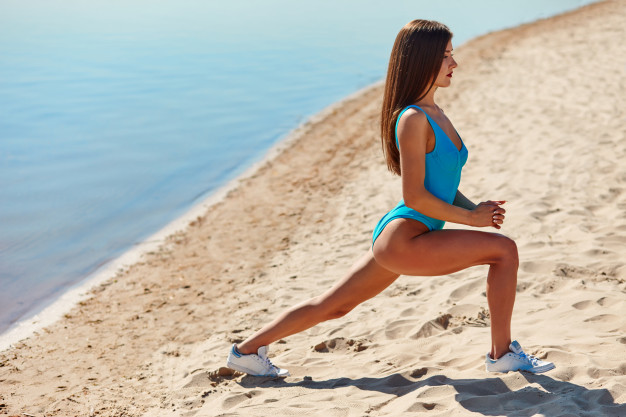portrait-beautiful-sporty-woman-swimwear-doing-workout-fitness-stretching-exercises-sand-beach-early-morning_251954-8